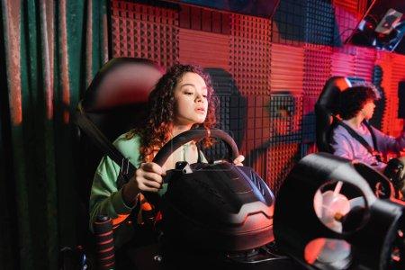 african american girl gaming on car simulator near blurred friend