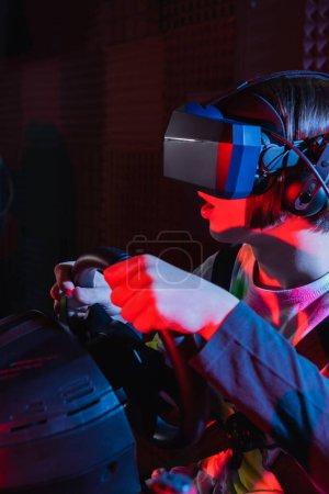 Photo pour Garçon étonné dans vr casque de jeu sur simulateur de course automobile avec bouche ouverte - image libre de droit