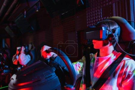 gamer in vr headset on car racing simulator near blurred friend