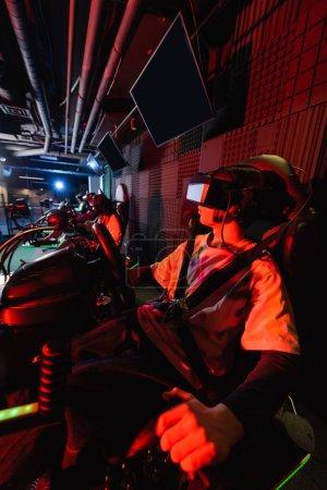 Photo for Teenage gamer racing in car simulator near blurred friends - Royalty Free Image