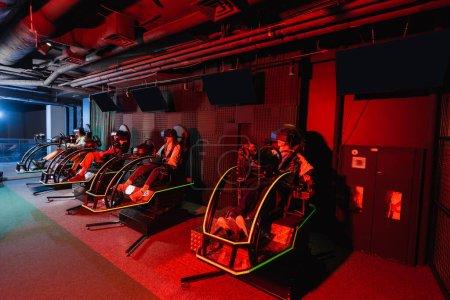 Photo pour Adolescents amis en réalité virtuelle casques de jeu sur simulateurs de course - image libre de droit