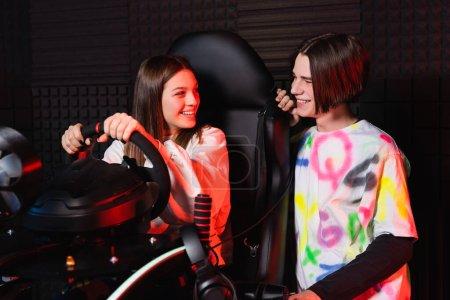 Photo pour Souriant adolescents parler près de voiture simulateur de course - image libre de droit