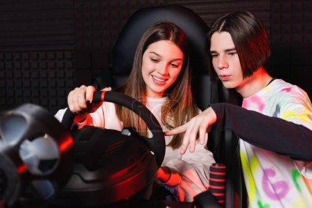 Photo pour Adolescent garçon pointant au volant de simulateur de voiture près ami souriant - image libre de droit