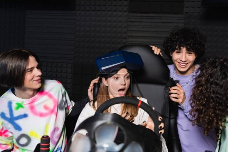 Photo pour Amis multiethniques riant près de fille étonnée sur simulateur de course de voiture - image libre de droit