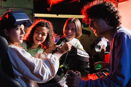 cheerful multicultural friends laughing near scared girl in racing simulator