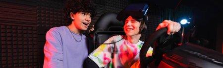 Photo pour Adolescent garçon parler à sourire gamer sur voiture simulateur, bannière - image libre de droit