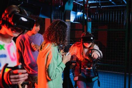 Photo pour Adolescent fille dans casque de jeu dans vr zone de jeu près de interracial amis - image libre de droit