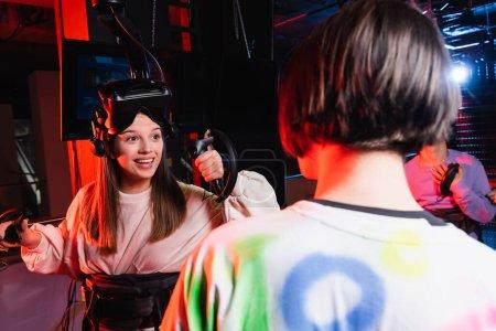 Photo pour Joyeuse fille souriant près des garçons adolescents dans la zone de jeu vr, premier plan flou - image libre de droit