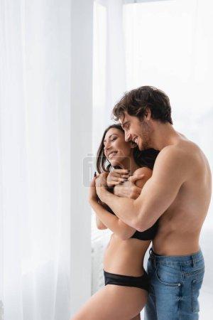 Lächelnder Mann in Jeans umarmt sinnliche Freundin mit geschlossenen Augen