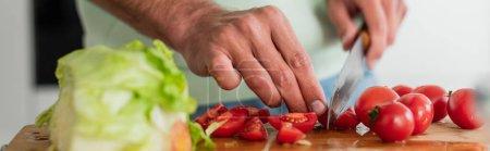 częściowy widok człowieka cięcia świeżych warzyw w kuchni, baner