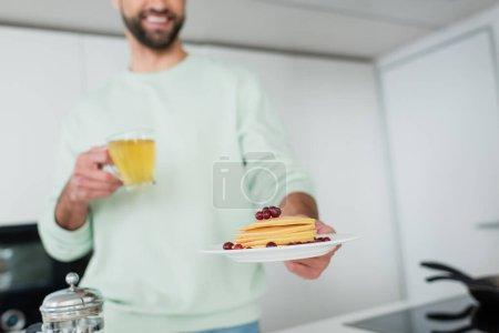 abgeschnittene Ansicht eines glücklichen verschwommenen Mannes mit grünem Tee und Teller mit Pfannkuchen