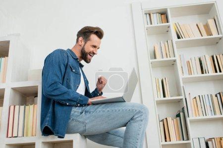 Photo pour Excité homme montrant geste ouais tout en regardant ordinateur portable - image libre de droit