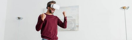 excited man showing yeah gesture while gaming in vr headset at home, banner