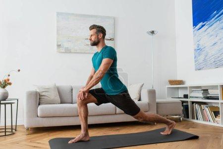 sportif homme pratiquant croissant lunge pose sur tapis de yoga à la maison