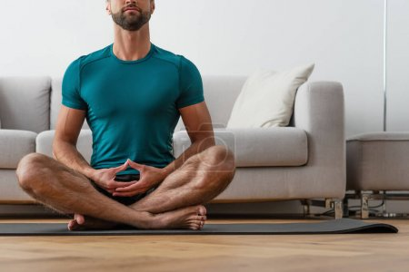 Photo for Cropped view of barefoot man meditating in lotus pose at home - Royalty Free Image