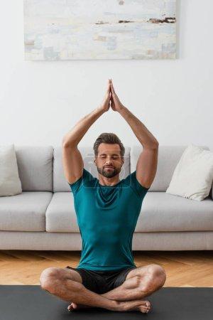 Photo pour Homme avec les mains priantes et les yeux fermés méditant dans la pose du lotus à la maison - image libre de droit