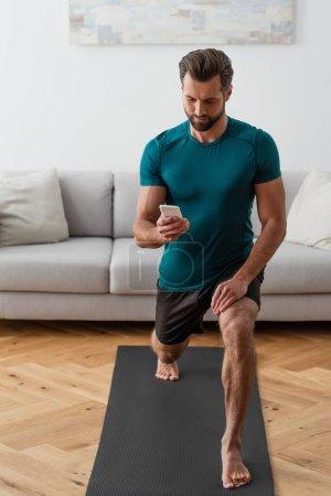 Photo pour Homme pieds nus regardant smartphone tout en pratiquant le yoga à la maison - image libre de droit