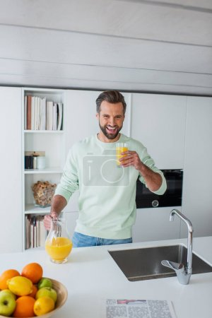Photo for Laughing man holding glass of fresh orange juice in kitchen - Royalty Free Image