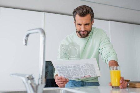 Photo pour Homme positif lisant le journal près du verre de jus d'orange et du robinet sur le premier plan flou - image libre de droit