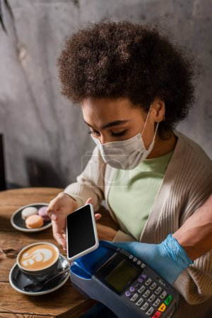 African american client in medical mask paying with smartphone near waiter with terminal in cafe