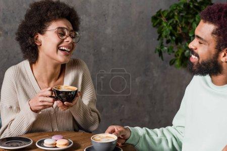 Alegre pareja afroamericana con café hablando cerca de macarrones en cafetería