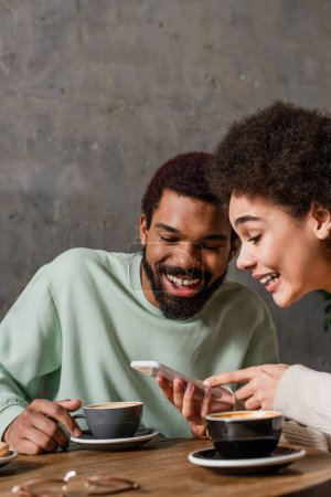 Positive african american couple using smartphone near cups of coffee in cafe