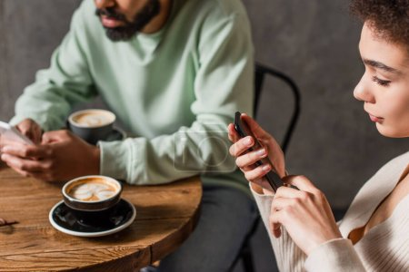 African american woman using cellphone near blurred coffee and boyfriend in cafe