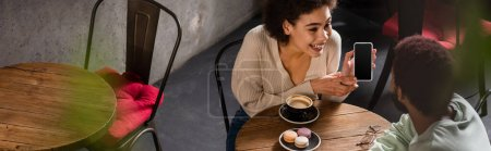 Smiling african america woman showing smartphone to boyfriend near coffee and macaroons in cafe, banner
