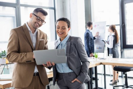 Cheerful businessman holding laptop near african american colleague in office