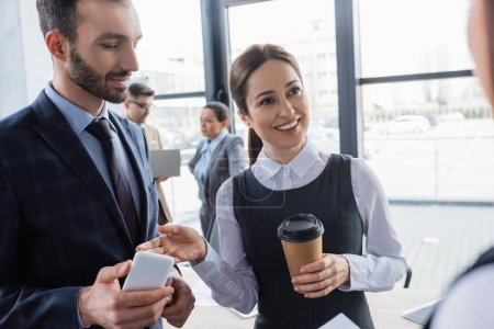 Cheerful businesswoman with coffee to go pointing at colleague with smartphone