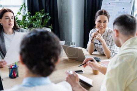 Photo pour Des femmes d'affaires souriantes regardant un collègue flou avec un ordinateur portable au bureau - image libre de droit