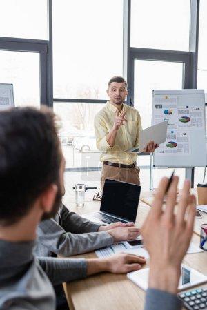 Photo pour Homme d'affaires avec ordinateur portable pointant vers un collègue sur le premier plan flou lors d'une réunion au bureau - image libre de droit