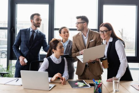 Photo for Smiling multiethnic business people with laptops talking in office - Royalty Free Image
