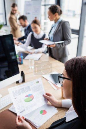 Photo pour Femme d'affaires tenant un document flou avec des graphiques près de collègues au bureau - image libre de droit