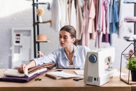 Photo pour Couture regardant le tissu près du portable, smartphone et machine à coudre - image libre de droit