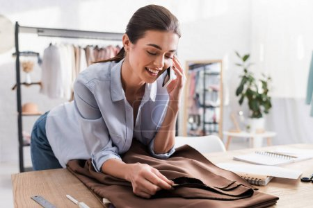 Photo for Cheerful seamstress talking on smartphone near fabric and notebook - Royalty Free Image