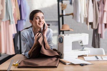 Photo pour Couture parler sur smartphone près de tissu, règle et machine à coudre - image libre de droit