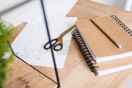 Skizzen neben Schere und Notizbuch auf dem Tisch