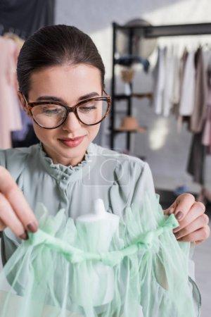 Photo pour Couture dans des lunettes tenant tissu près du mannequin flou - image libre de droit