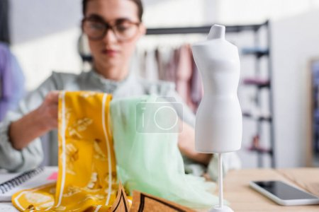 Photo for Mannequin near blurred designer with fabric in atelier - Royalty Free Image