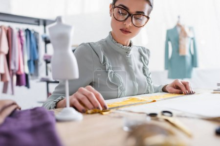 Photo for Seamstress holding ruler near fabric and blurred mannequin - Royalty Free Image