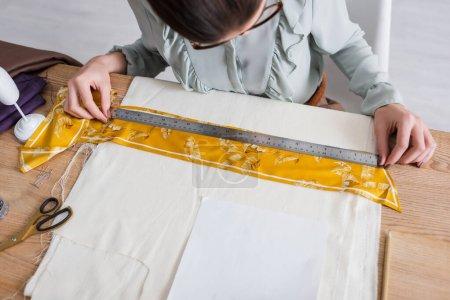 Hohe Winkelansicht des Designers, der mit Lineal und Stoff in der Nähe der Schere auf dem Tisch arbeitet
