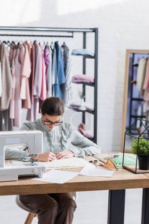 Photo pour Tissu de marquage designer tout en travaillant près de croquis et machine à coudre en studio - image libre de droit