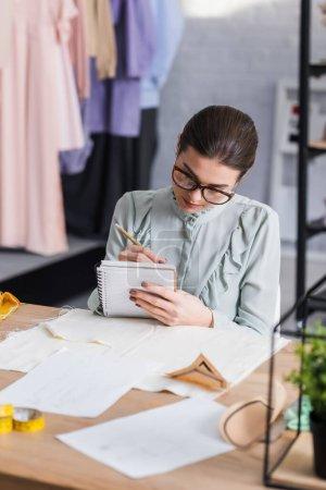Designer écriture sur carnet près de tissu et motifs de couture sur la table