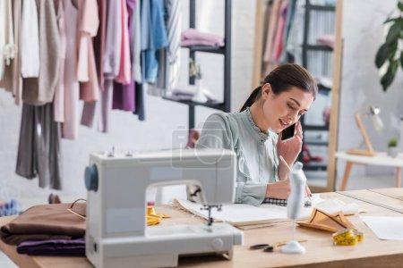 Photo pour Designer parler sur smartphone et écrire sur ordinateur portable près du tissu et de l'équipement - image libre de droit