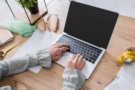 Photo pour Vue recadrée de la couturière à l'aide d'un ordinateur portable près du ruban à mesurer et croquis sur la table - image libre de droit