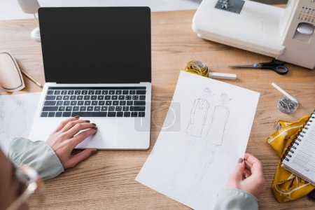 Blurred designer using laptop and holding sketches in atelier