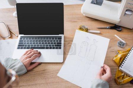 Photo pour Designer flou utilisant un ordinateur portable et tenant des croquis en atelier - image libre de droit