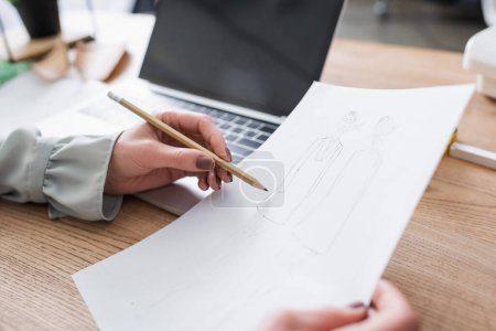 Photo pour Vue recadrée du croquis de dessin de concepteur près d'un ordinateur portable flou sur la table - image libre de droit