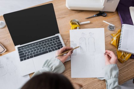 Photo pour Vue aérienne des croquis de dessin de concepteur près de l'ordinateur portable et de la machine à coudre - image libre de droit